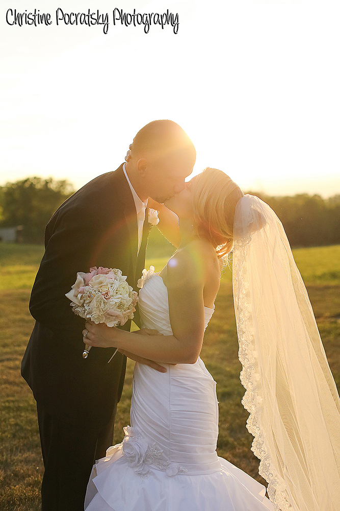 Photo Bride and groom kissing at sunset