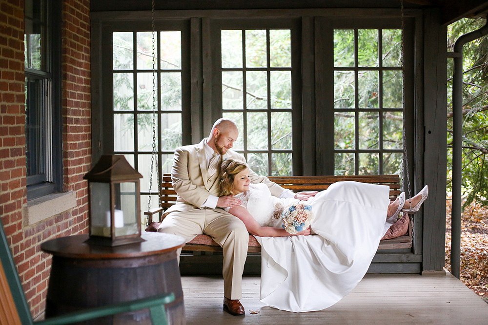Bride and groom on bench in front of windows.