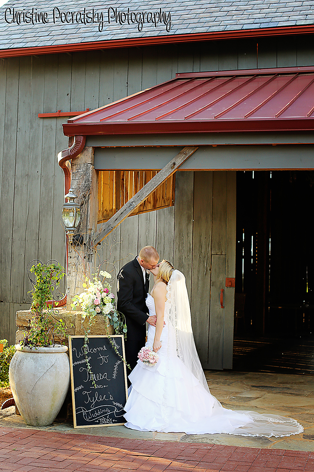 Phot Bride and groom kissing in front of barn.