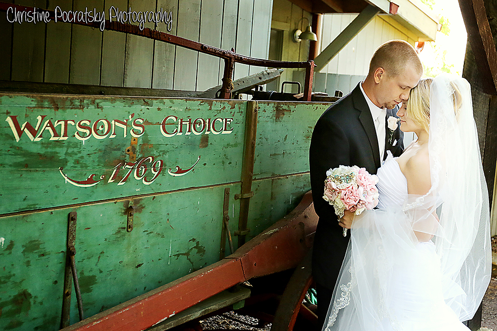 Photo Bride and Groom standing in front of chuck wagon.
