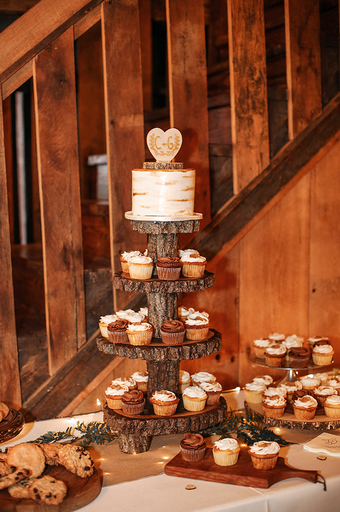 Photo of wedding cake, cup cakes in side the barn.