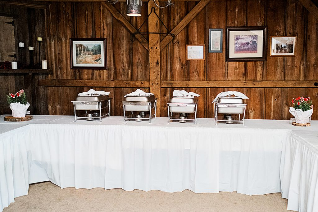 The buffet table with white linens and four hot plates.