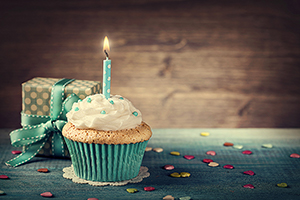 Cupcake with a birthday candle and a gift in background
