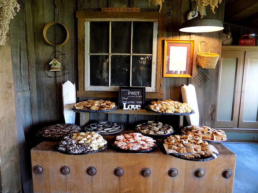 A butcher block table used to display cupcakes and cookies