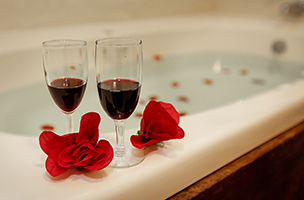 two glasses of wine and 2 roses