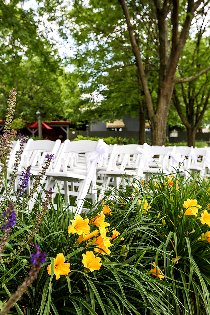 Photo Flowers in front of chairs by Pergola.