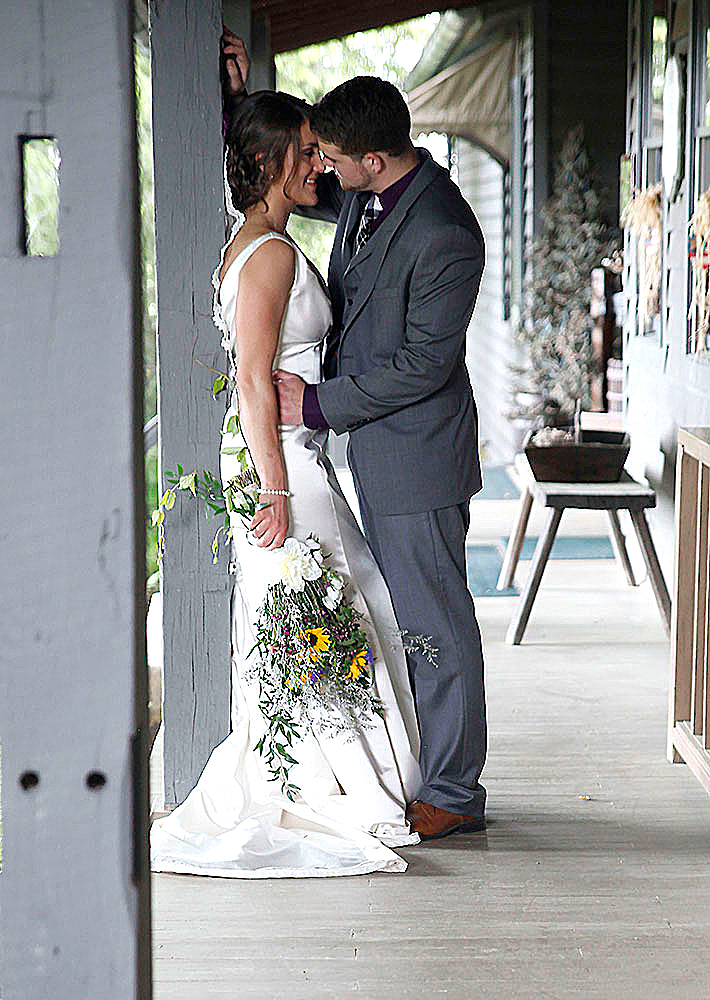 Bride and groom kissing on t the porch.