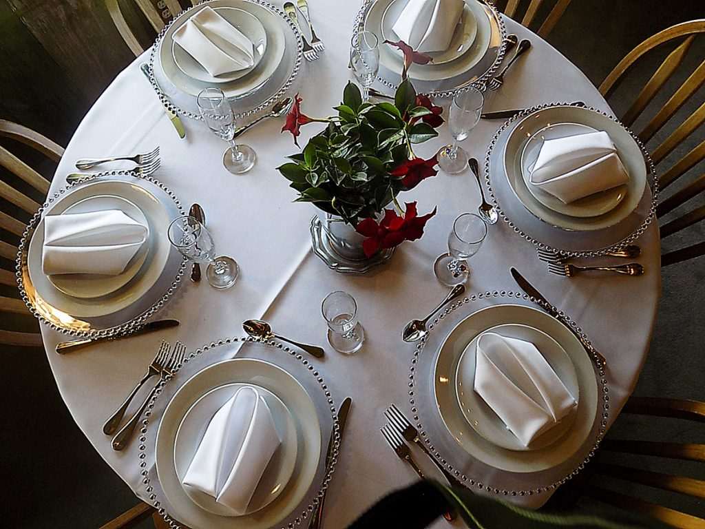 A round top table set with formal wear