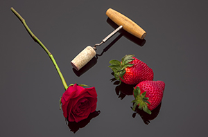 Strawberries roses and wine cork.