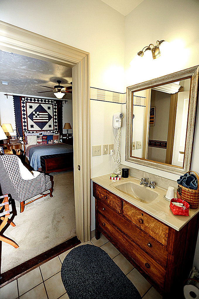 Americana Queen room Bathroom sink and chair.